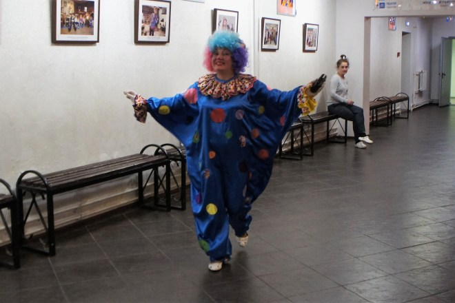 A character dressed in a blue onsie covered in coloured circles wearing a curly blue wig on the tree ornament factory tour in Klin Russia