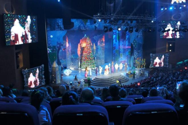 Seats in a theatre auditorium raked down towards a stage which a large decorated tree and festive characters including Ded Moroz
