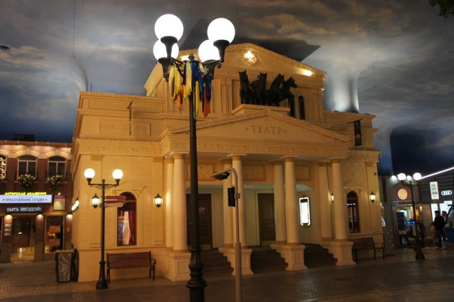 A mock up of the Bolshoi theatre inside the KidZania Moscow themepark. The blue sky and white clouds are painted on the ceiling and there is a streetlamp in the foreground.