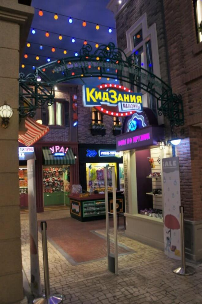 KidZania Moscow shopping area with small colourful shops lit by neon signs