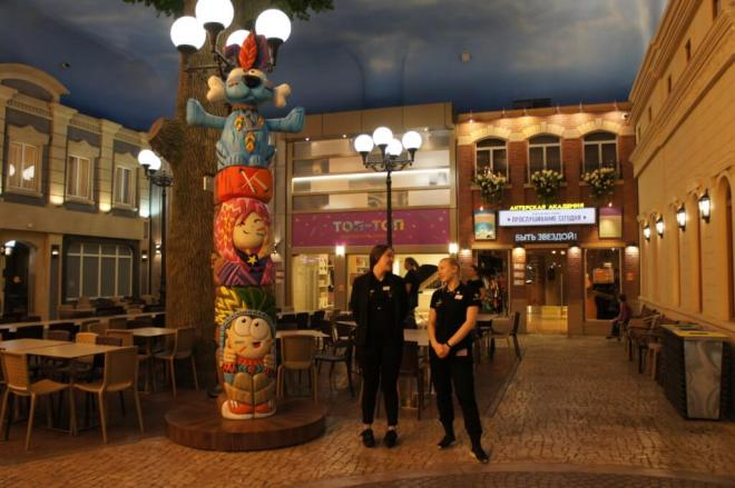 Two adult KidZania Moscow workers stand smiling at each other in front of a theatre school and fashion studio next to a cartoon themed totem pole