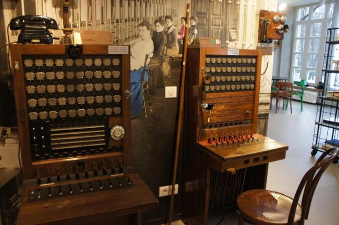Two early telephone switchboards in front of a photograph of women operating them at the Museum of Telephone History in Moscow