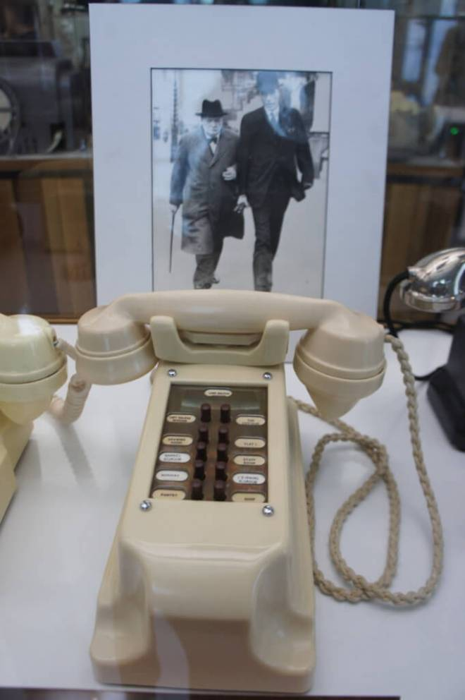 White telephone from a stately home for summoning staff with a photo of Winston Churchill