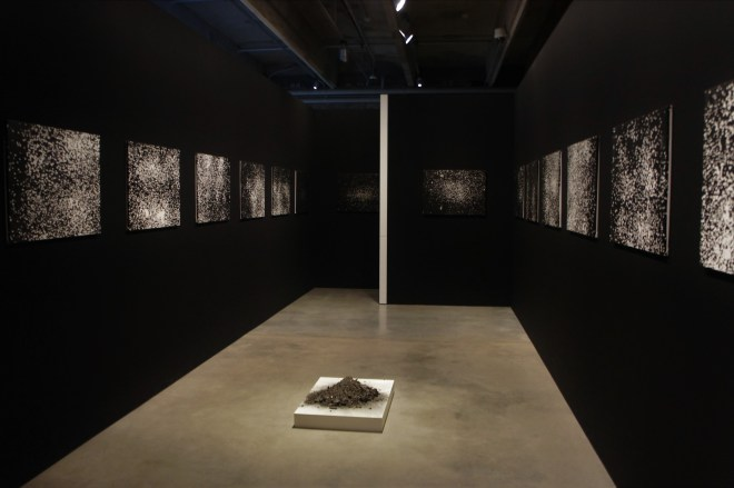 A dark room with back and white paintings of white splodges and a pile of ashes on the floor
