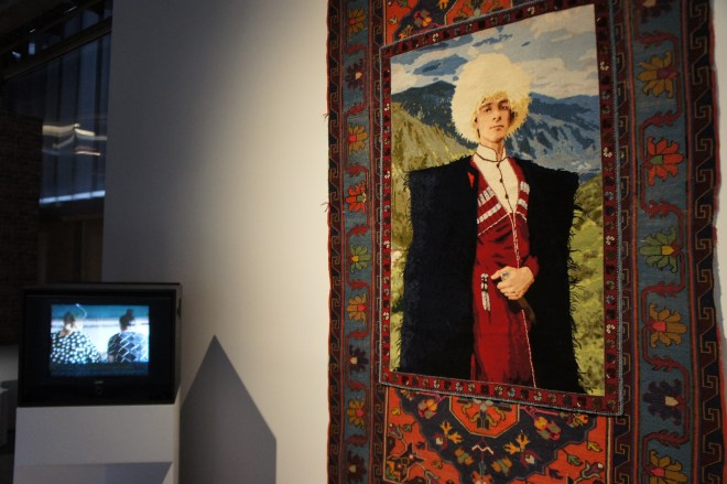Handmade rug portrait of a man from the Caucuses, with a TV showing a film of the rug being made