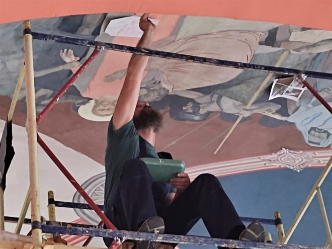 A man sitting on scaffolding, decorating the ceiling of a Russian Orthodox church