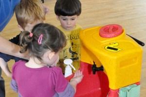 Children washing hands in nursery school with mobile sink
