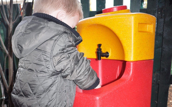 Children washing hands outdoors with portable sinks