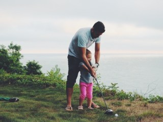 Dad and daughter playing golf