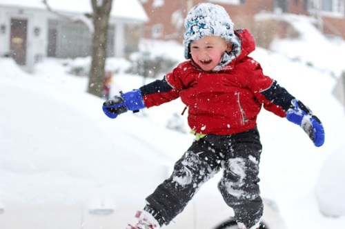 Daddy throwing his boys into snow piles by Jennifer Beilman