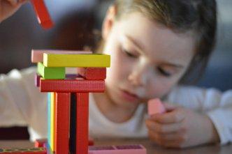garde d'enfants périscolaire : une petite fille qui joue avec des blocs en bois