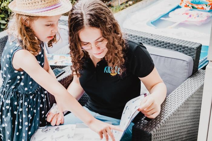 Recherche babysitter : une nounou top Kidlee avec la petite fille qu'elle garde en train de découvrir le contenu d'un livre ensemble