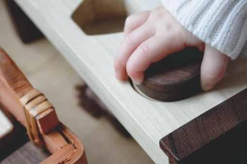 Pédagogie Montessori : main d'un enfant sur un outil Montessori