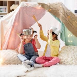 deux petites filles qui s'amusent sous une cabane construite avec des plaides et des draps