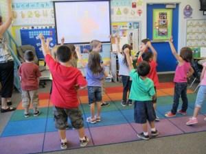 children raising hands in the classroom