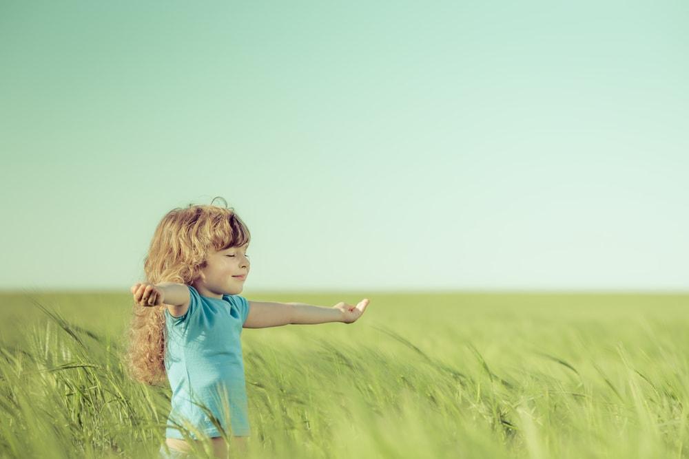 女の子が草原で手を広げている様子