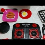Toy kitchen set for kids. Little boy unboxing and cooking eggs .