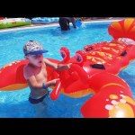 Kids playing in water with inflatable lobster toy. Funny video on the beach and to the pool.