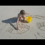 Kids playing on the beach. They drawing smiley faces in sand. Family fun video 2017
