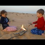 Kids playing with sand in the desert. They pretend  have slides, and do fire. Video 2017