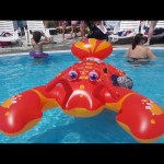 Kids playing in water with inflatable lobster. Fun in the pool and on the beach