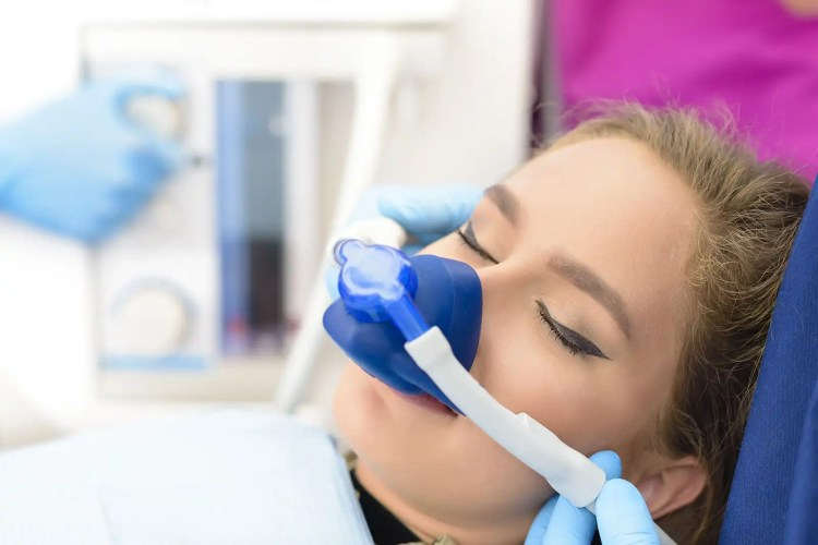 A young woman wears a nitrous oxide mask.