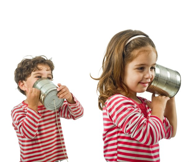 boy and girl talking on a tin phone isolated on white