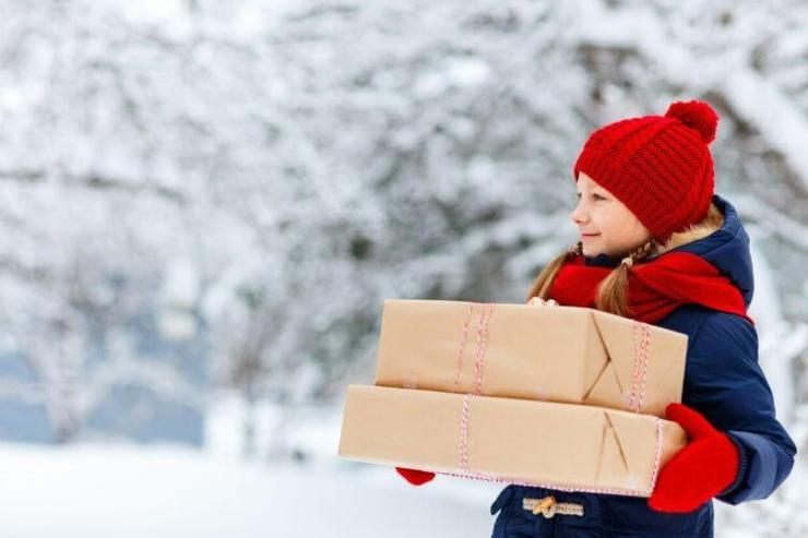 girl carrying gifts in the snow