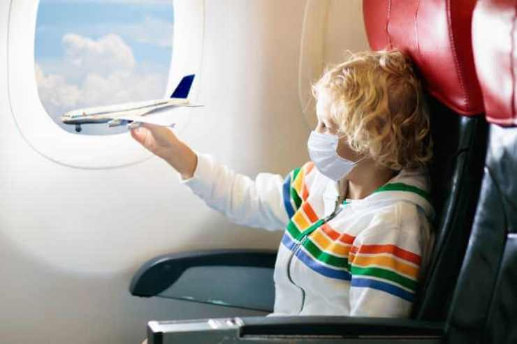 Child wearing mask on airplane-Kids Are A Trip