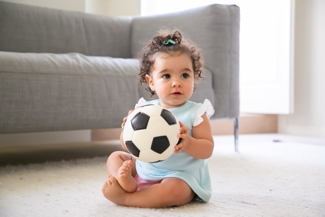 adorable black haired baby girl pale blue clothes sitting floor home looking away playing soccer ball kid home childhood concept
