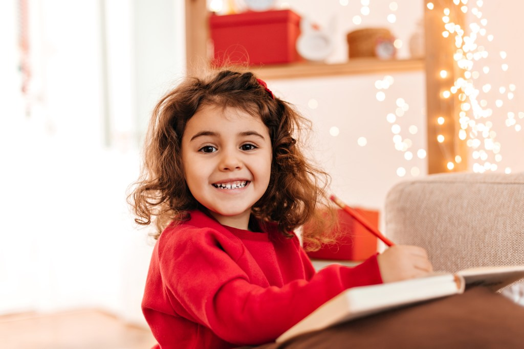excited kid drawing with smile indoor shot brunette child with pen notebook