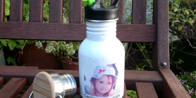 Image of white water bottle with photo of girl on it, black cap and green straw on garden bench