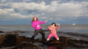 Image of woman and child doing air guitar on seaweed at beach