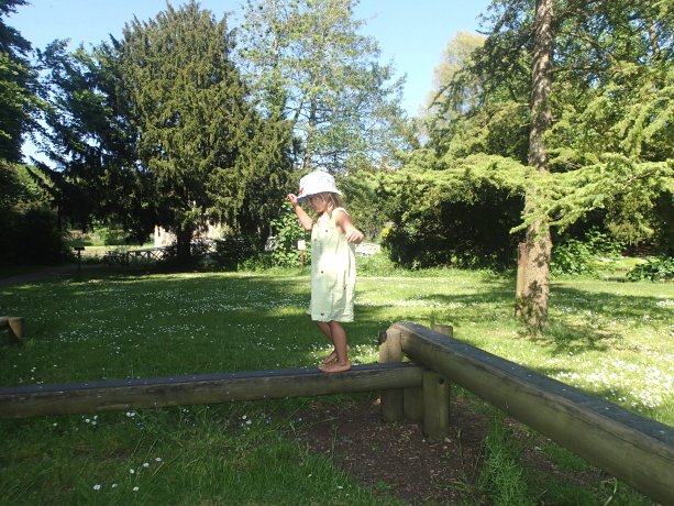 Image of barefoot girl in sundress and sunhat on outdoor balance beam