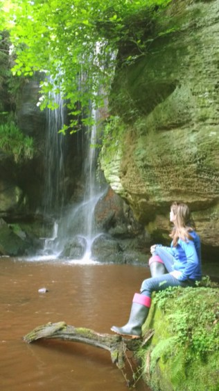 Image of woman in blue clothes and wellies sitting by steep waterfall with trees overhanging