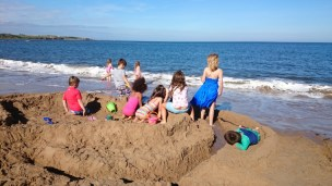 Image of group of children-sitting-on-large-sand-castle-on-beach-hogwarts