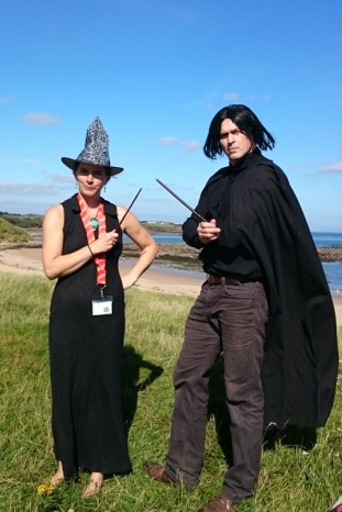 Image of couple-overlooking-beach-in-witch-outfits-mcgonogall-and-snape-costume