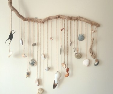 Image of driftwood-branch-with-hanging-beach-treasures-mobile-on-wall