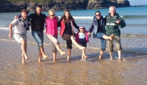 family-paddling-in-sea-with-cliffs-in-background