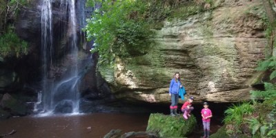 Image of woman and children standing on rock near waterfall
