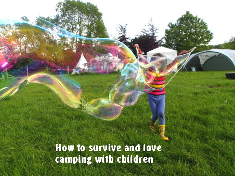 Image of girl in stripy top, blue leggings and yellow wellies-blowing-giant-bubbles-in-field-with-tent-and-tipi-behind with words How to survive and love camping with children