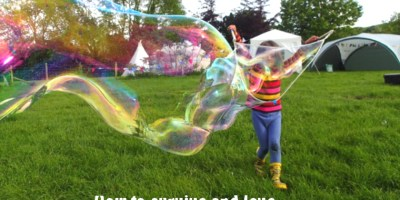 Image of girl ins tripy top, blue leggings and yellow wellies-blowing-giant-bubbles-in-field-with-tent-and-tipi-behind with words How to survive and love camping with children