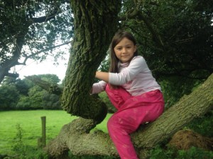 girl in tree with fields behind