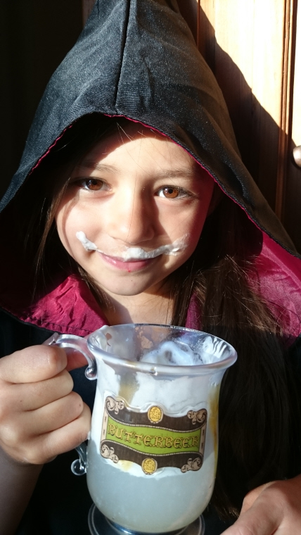 girl-in-witch-outfit-drinking-from-a-tankard-with-butter-beer-writing-on-it