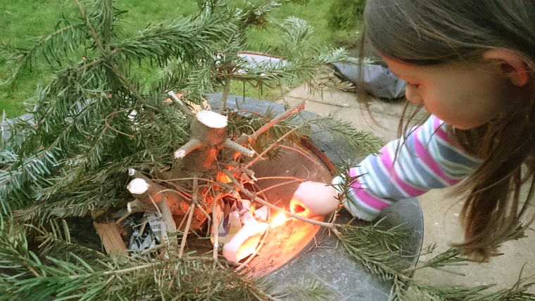Image of girl-lighting-evergreen-branches-in-firepit