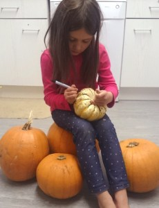 girl-sitting-on-pumpkins-drawing-design-onto-one