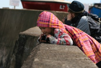 Image of girl-with-binoculars-leaning-over-harbour-wall