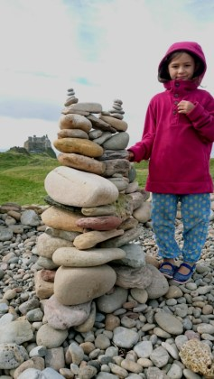 Image of girl-with-cairn-of-stones-with-caastle-in-background-holy-island