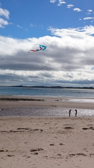 Image of girls-in-distance-on-beach-flying-a-kite