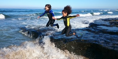 Image of two girls-in-wetsuits-leaping-from-rocks-into-foaming-sea